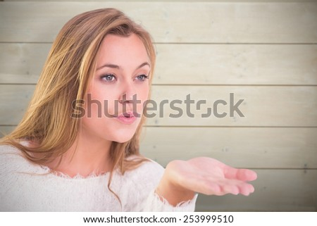 Pretty blonde blowing a kiss against bleached wooden planks background - stock photo