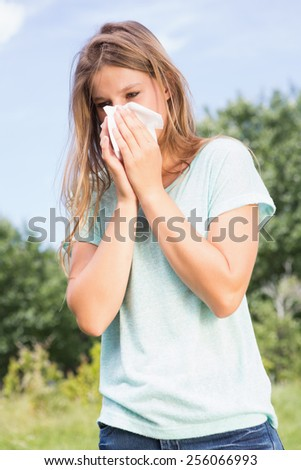 Pretty blonde blowing her nose on a sunny day
