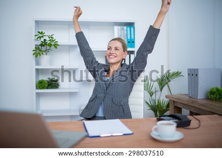 Pretty blonde businesswoman gesturing victory at office