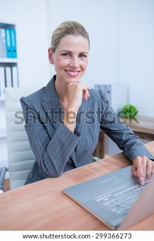 Pretty blonde businesswoman using her laptop at the office