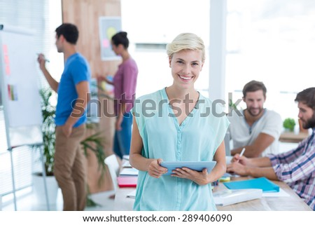 Pretty blonde businesswoman using tablet in the office - stock photo