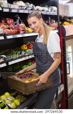 Pretty blonde carrying boxes of fresh vegetables in the supermarket
