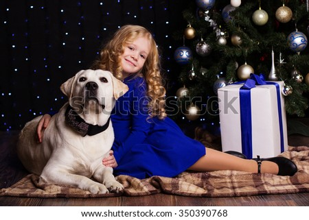 Pretty blonde child girl with her friend white labrador dog are sitting near christmas tree at home - stock photo