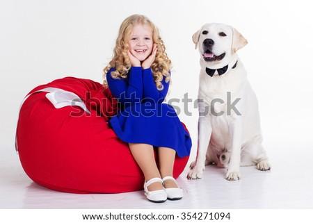 Pretty blonde child girl with her friend white labrador retriever are sitting in studio isolates on white  - stock photo