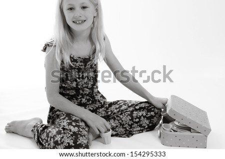 pretty blonde child having a tea party, isolated on white background in monochrome