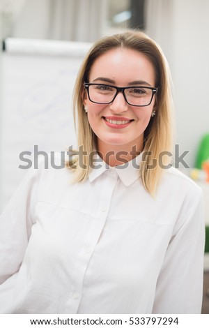 Pretty blonde designer smiling at camera in creative office
