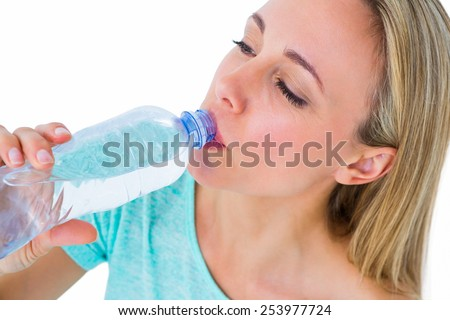 Pretty blonde drinking from her water bottle on white background