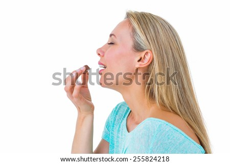Pretty blonde eating a chocolate on white background - stock photo