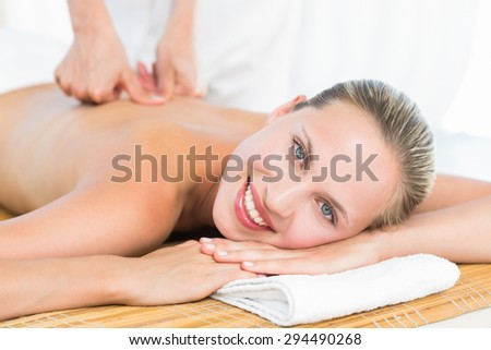 Pretty blonde enjoying a massage smiling at camera at the health spa