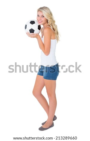 Pretty blonde football fan holding ball on white background - stock photo