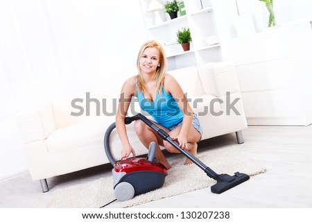 Pretty blonde girl cleans the living room with the vacuum cleaner - stock photo