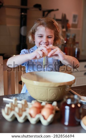 Pretty blonde girl haired cracking an egg into a mixing bowl