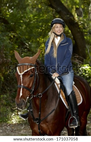 Pretty blonde girl horseback riding in the woods.