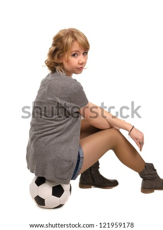 Pretty blonde girl in shorts sitting on a soccer ball looking back over her shoulder at the camera , studio portrait isolated on white - stock photo