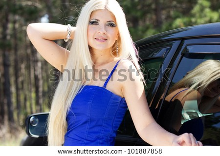 Pretty blonde girl near the car
