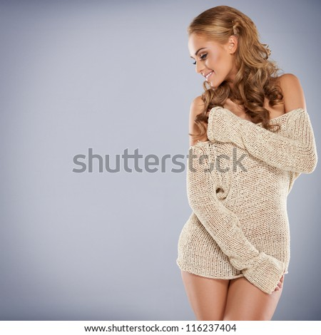 Pretty blonde girl posing while isolated against a grey background