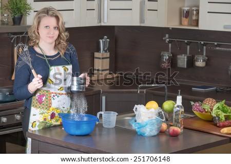 Pretty blonde girl prepares at home kitchen - stock photo