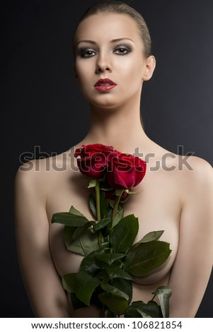 pretty blonde girl's low key portrait with three red roses, she is in front of the camera, looks in to the lens and takes the roses in the center of the chest - stock photo