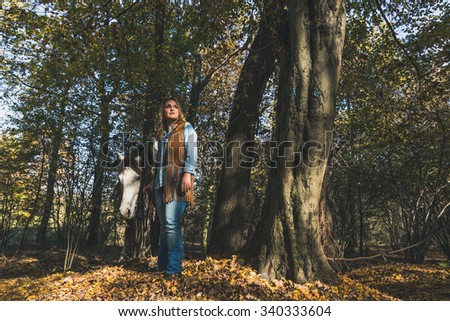 Pretty blonde girl standing by her grey horse in the countryside - stock photo
