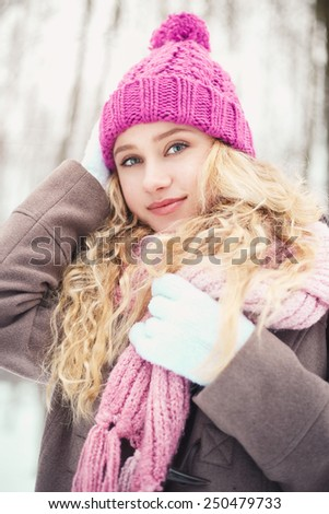 Pretty blonde girl walking in a winter park
