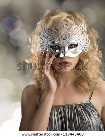 pretty blonde girl with curly hair takes one silver mask, she is in front of the camera and takes the mask on the face with right hand - stock photo