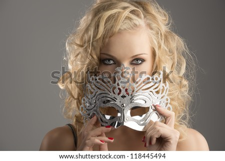 pretty blonde girl with curly hair takes one silver mask, she is in front of the camera, takes the mask on the mouth and looks in to the lens - stock photo