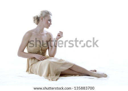 pretty blonde girl with elegant dress sitting on white floor, isolated on white - stock photo