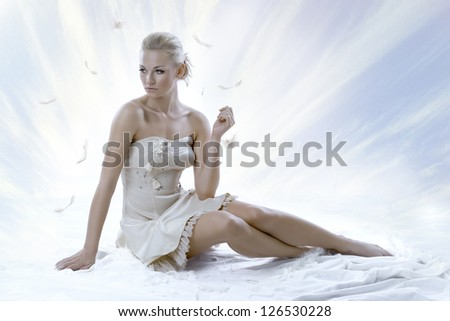 pretty blonde girl with elegant dress sitting on white floor, with a sky as a background Her face is turned of three quarters at right and she looks down - stock photo
