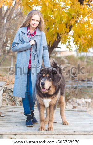 Pretty blonde girl with mastiff on the nature