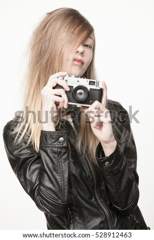 Pretty blonde girl with messy hair holding vintage camera wearing black leather jacket.