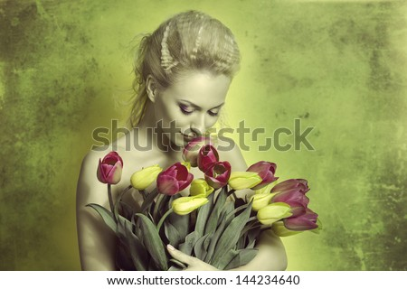pretty blonde girl with pretty hair-style and coloured makeup taking bouquet of tulips and smelling tunned in green color - stock photo
