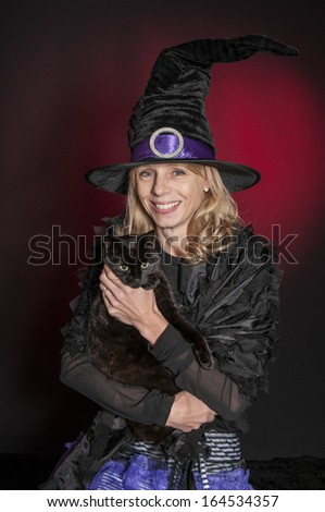 pretty blonde Halloween witch with a black cat isolated on dark red background