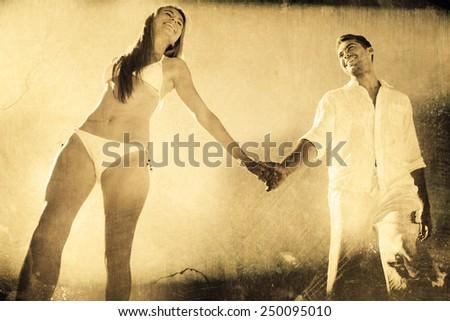 Pretty blonde holding hands with boyfriend against grey background - stock photo
