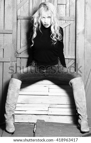 Pretty blonde in jeans and boots with long curly hair sitting and posing near wooden wall, black and white