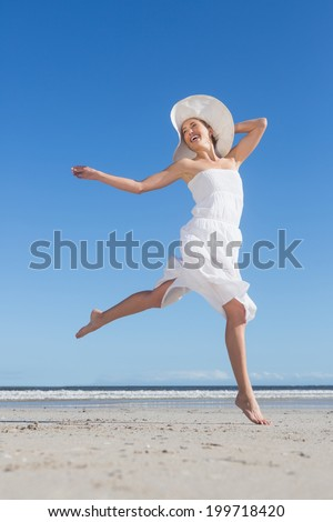 Pretty blonde in white dress leaping on the beach on a bright day - stock photo