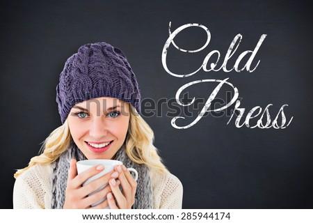 Pretty blonde in winter fashion holding mug against black background - stock photo