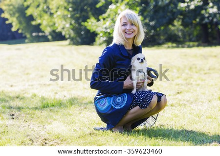 Pretty blonde lady holding her scared chihuahua - stock photo