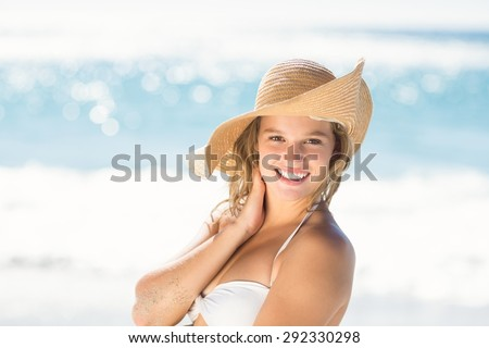 Pretty blonde looking at camera at the beach - stock photo
