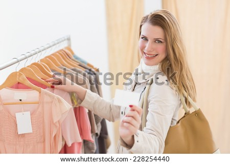 Pretty blonde looking at clothes on rail in the store - stock photo