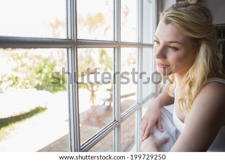 Pretty blonde looking out the window at home in the living room