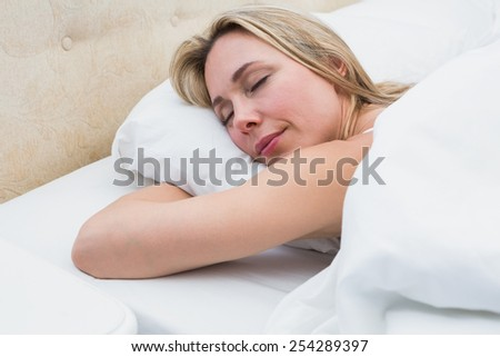 Pretty blonde lying in bed sleeping at home in the bedroom