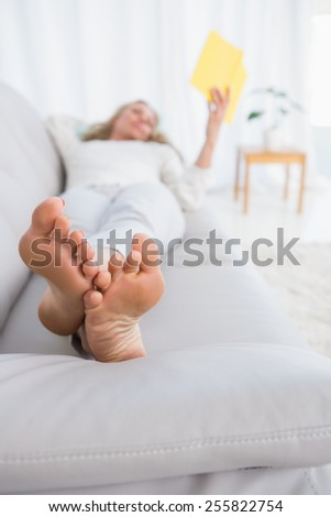 Pretty blonde lying on couch reading book at home in the living room - stock photo