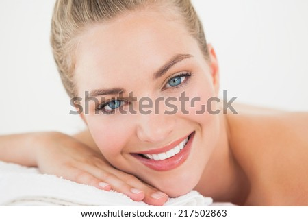 Pretty blonde lying on massage table smiling at camera at the health spa
