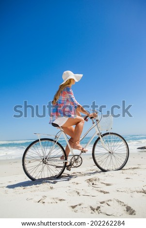 Pretty blonde on a bike ride at the beach on a sunny day - stock photo