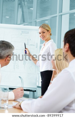 Pretty blonde presenting plan to her co-workers - stock photo
