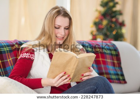 Pretty blonde reading book at christmas time at home in the living room