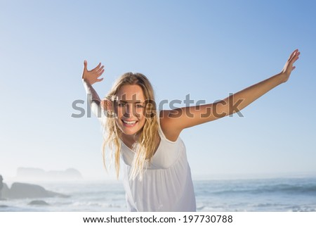Pretty blonde smiling at the beach in white sundress on a sunny day - stock photo