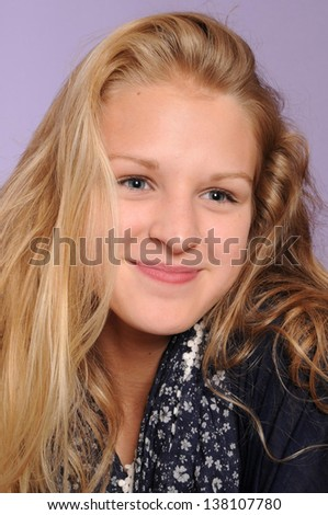 pretty blonde smiling teenage girl isolated on lilac background