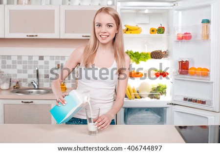 Pretty blonde standing near open fridge full of food. Young woman looking at camera, smiling and holding glass of milk