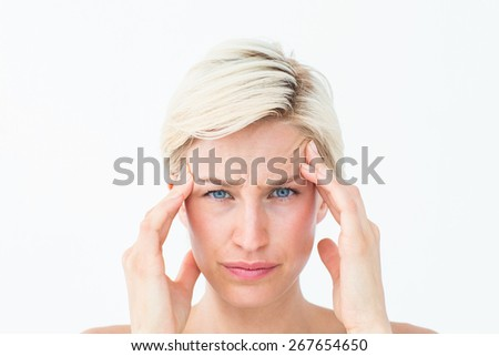Pretty blonde suffering from headache looking at camera on white background